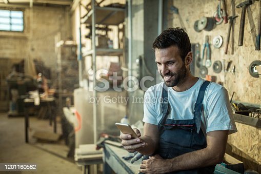 Manual worker surfing the Internet on a cell phone at workshop.
