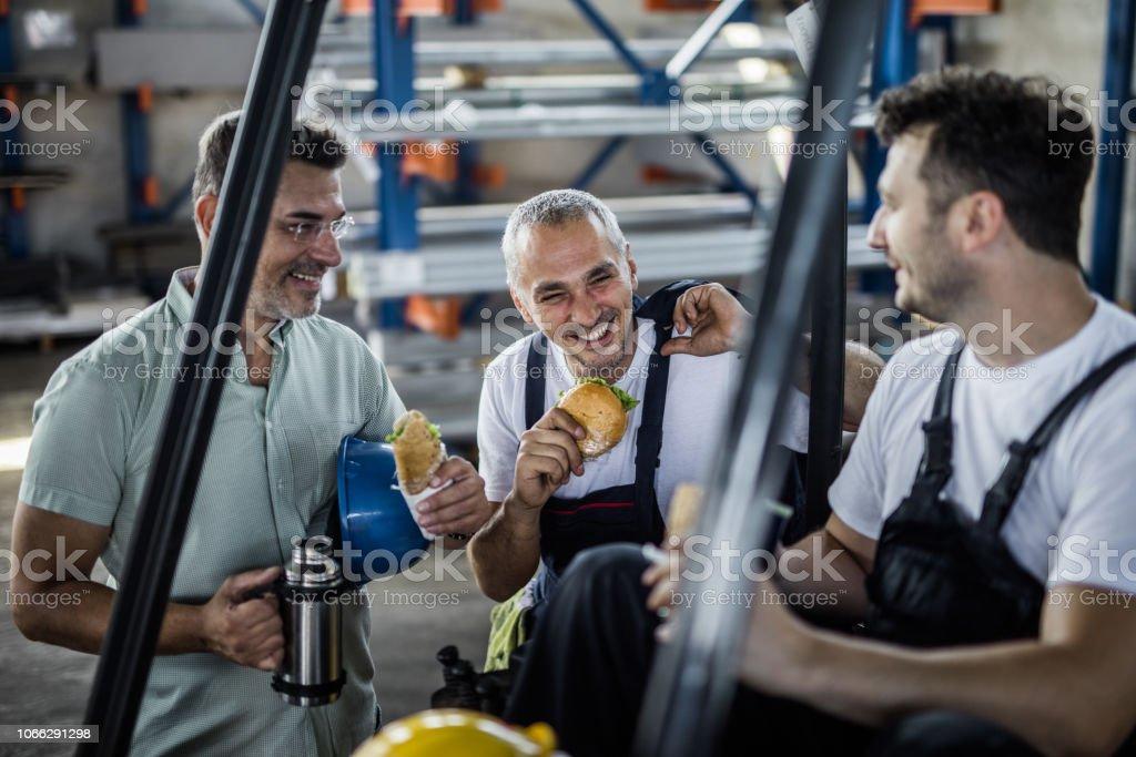 Glückliche Arbeiter und ihre Manager sprechen auf ein Mittagessen in einer Fabrik zu brechen. – Foto