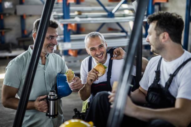 glada arbetare och deras manager talar på en lunch paus i en fabrik. - lunchrast bildbanksfoton och bilder