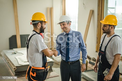 961745166istockphoto Happy manual workers came to an agreement with an architect at construction site. 1072908798
