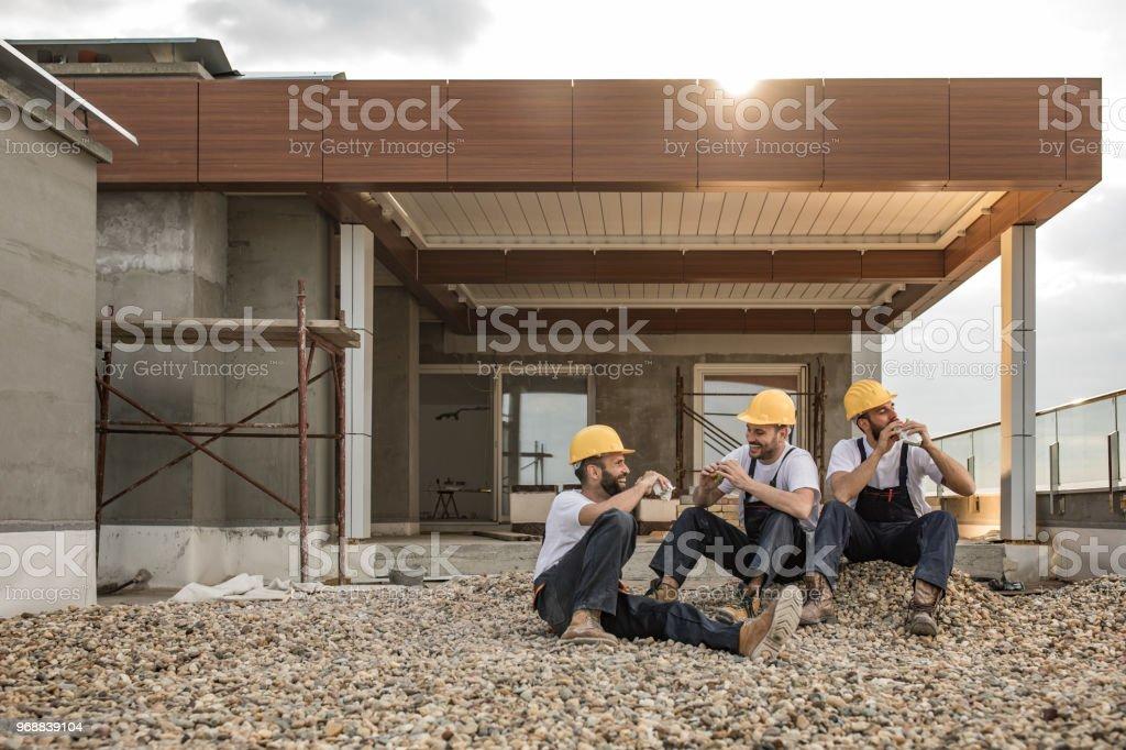 Glückliche Arbeiter Essen Sandwiches auf eine Mittagspause im Penthouse-Terrasse. – Foto
