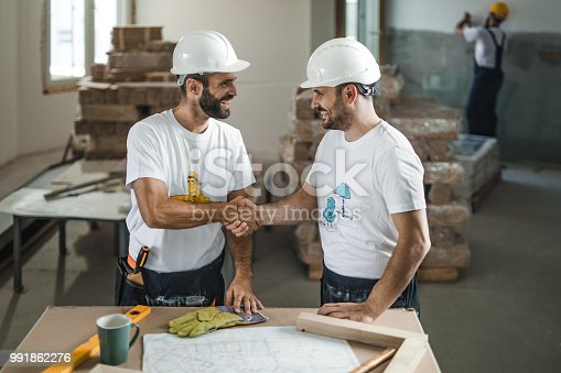 961745166istockphoto Happy manual workers greeting each other on construction site. 991862276