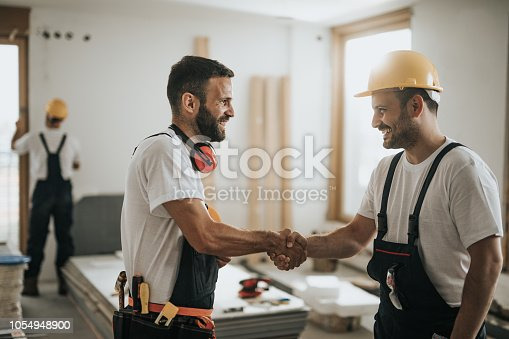 961745166istockphoto Happy manual workers shaking hands at construction site. 1054948900