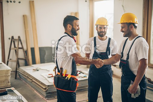 961745166istockphoto Happy manual workers shaking hands at construction site. 1072903374