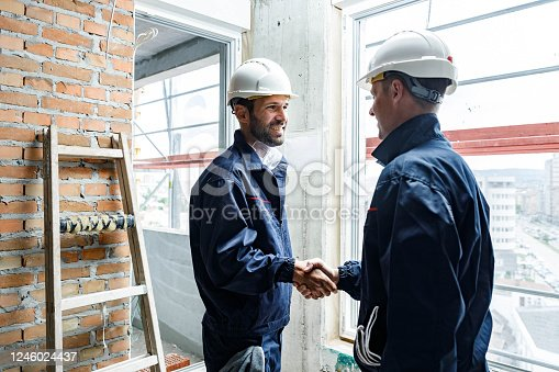 961745166 istock photo Happy manual workers shaking hands at construction site. 1246024437