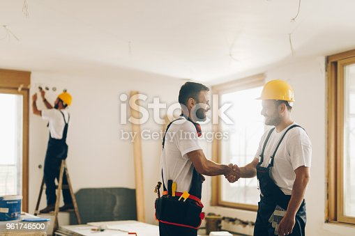 961745166istockphoto Happy manual workers shaking hands at construction site. 961746500
