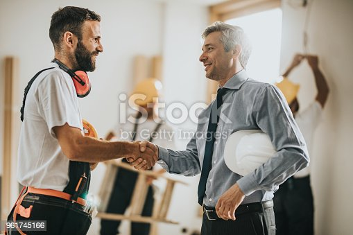 istock Happy manual workers shaking hands with an architect at construction site. 961745166