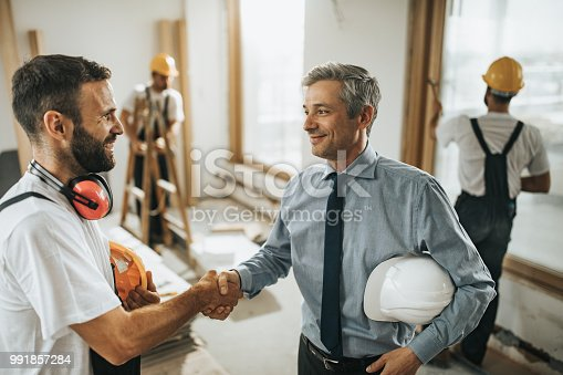 961745166istockphoto Happy manual workers shaking hands with an architect at construction site. 991857284