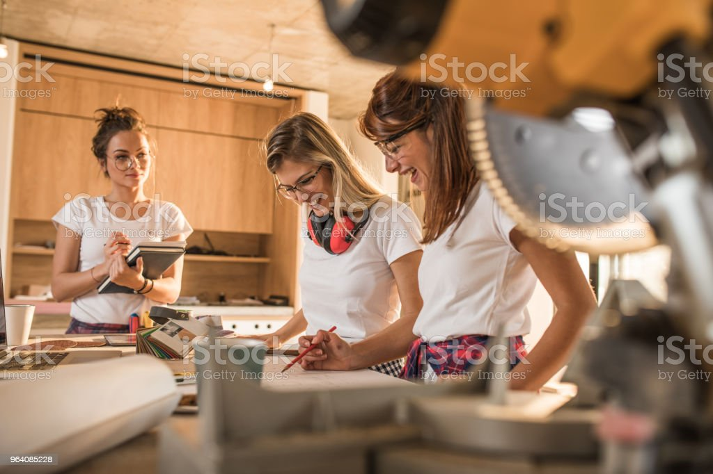 Happy manual workers standing at construction site and analyzing blueprints. - Royalty-free Adult Stock Photo