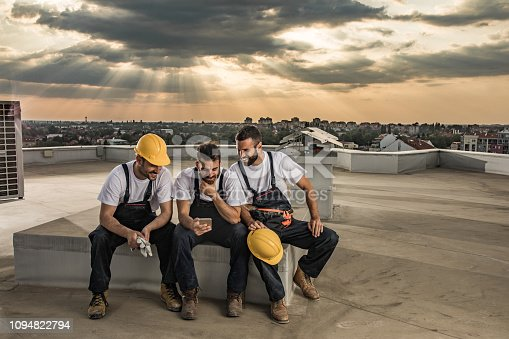 Young happy construction workers relaxing on a rooftop and reading text message on cell phone.