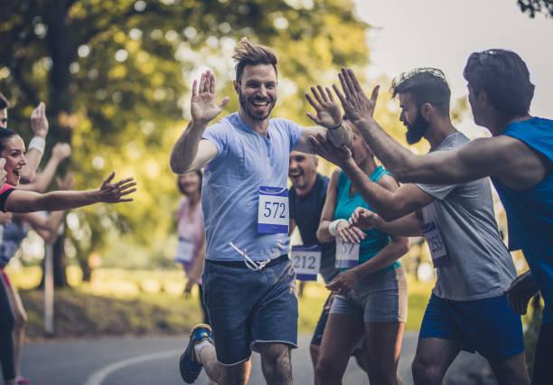grupo de atletas en línea de meta en feliz maratón corredor saludo. - maratón fotografías e imágenes de stock