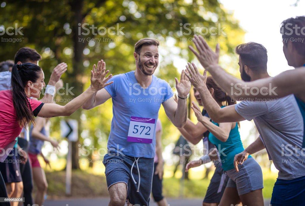 Feliz maratona corredor saudação grupo de atletas na linha de chegada. - foto de acervo