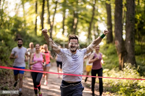 istock Happy marathon runner winning and crossing finish line with arms raised. 866901922