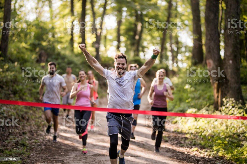 Maratonista feliz ganhar a corrida e cruzar a linha de chegada com braços erguidos. - foto de acervo
