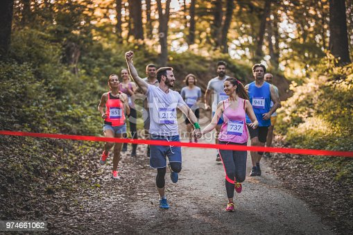 istock Happy marathon runners holding hands while running through finish line together. 974661062