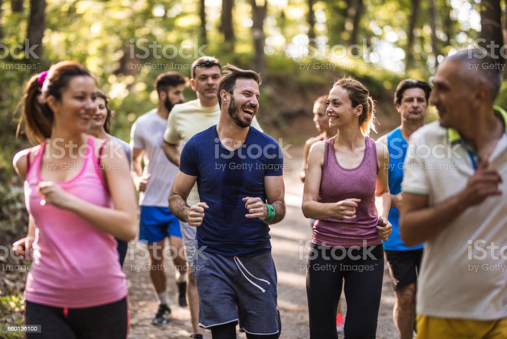 Happy marathon runners talking while running through the forest. stock photo
