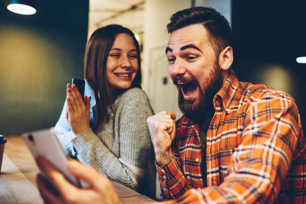 Happy marriage celebrating victory in internet lottery watching online broadcast on smartphone with winning results.Amazed hipsters wondered with win in online auction betting on website on phone stock photo