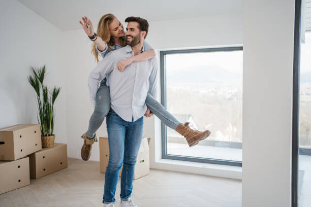 Happy married couple celebrating their first house purchasing stock photo