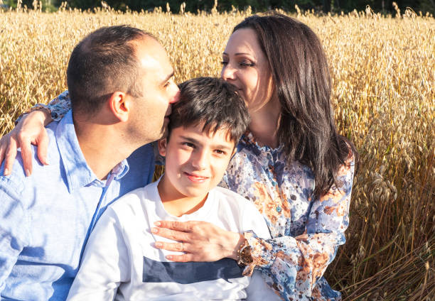 Happy married couple hug their son, arabs. At a picnic in the oats field. Happy married couple hug their son, arabs. At a picnic in the oats field. armenian ethnicity stock pictures, royalty-free photos & images
