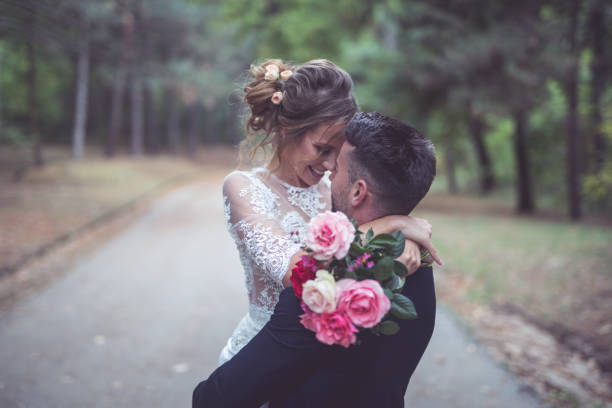 happy married couple Groom is holding a bride in his arms and spinning her around spinning in the park on their wedding day bridegroom stock pictures, royalty-free photos & images