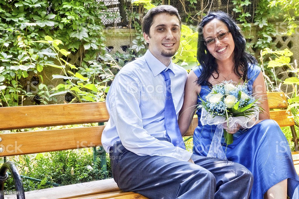 Happy married couple sitting on bench royalty-free stock photo