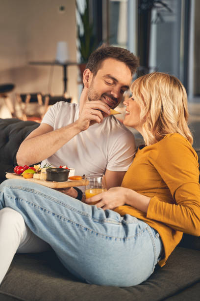 Happy married people eating together on the sofa stock photo
