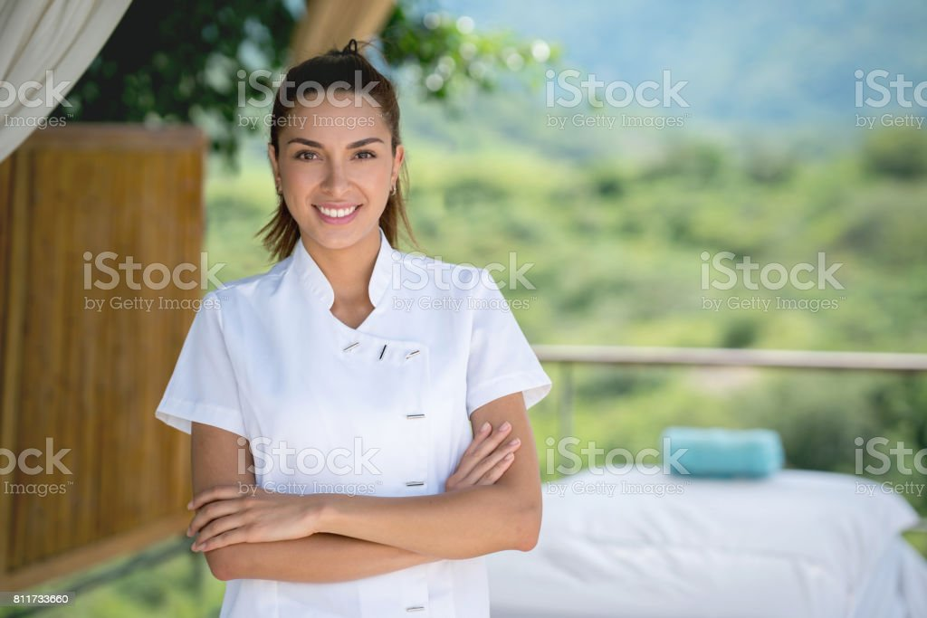 Happy masseuse working at an outdoor spa stock photo
