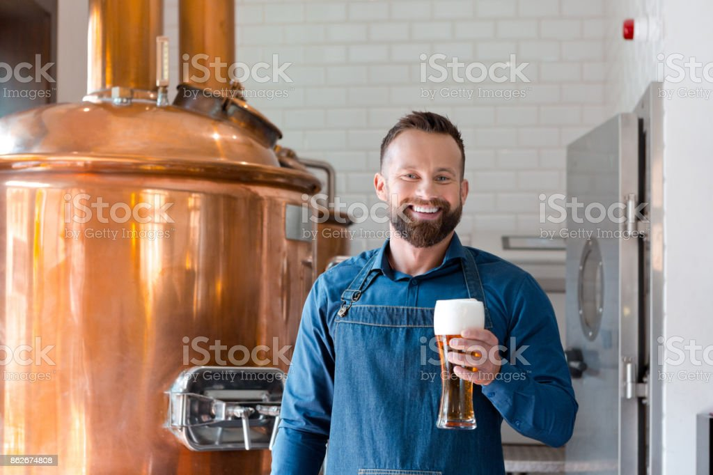 Happy master brewer holding beer glass in his micro brewery Happy master brewer standing in front of copper vat and holding beer glass in his micro brewery. Adult Stock Photo