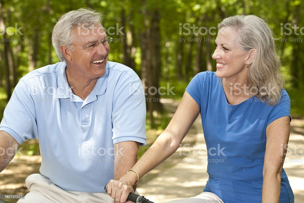 Happy Mature Adult Couple Biking Together royalty-free stock photo