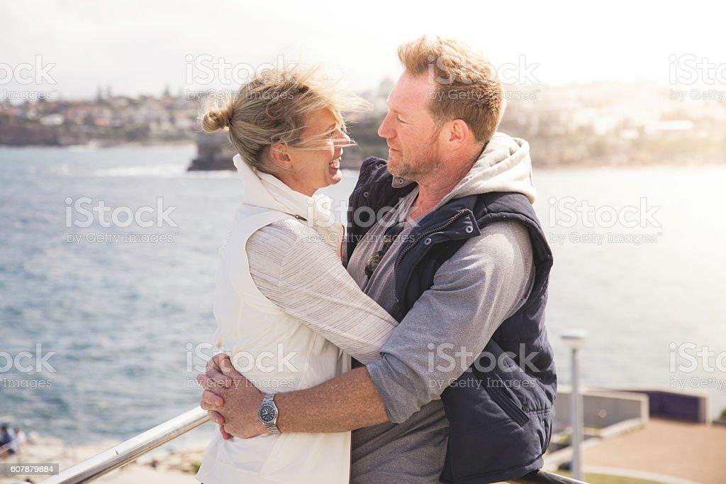 Happy mature adult couple embracing in warm coastal sun stock photo