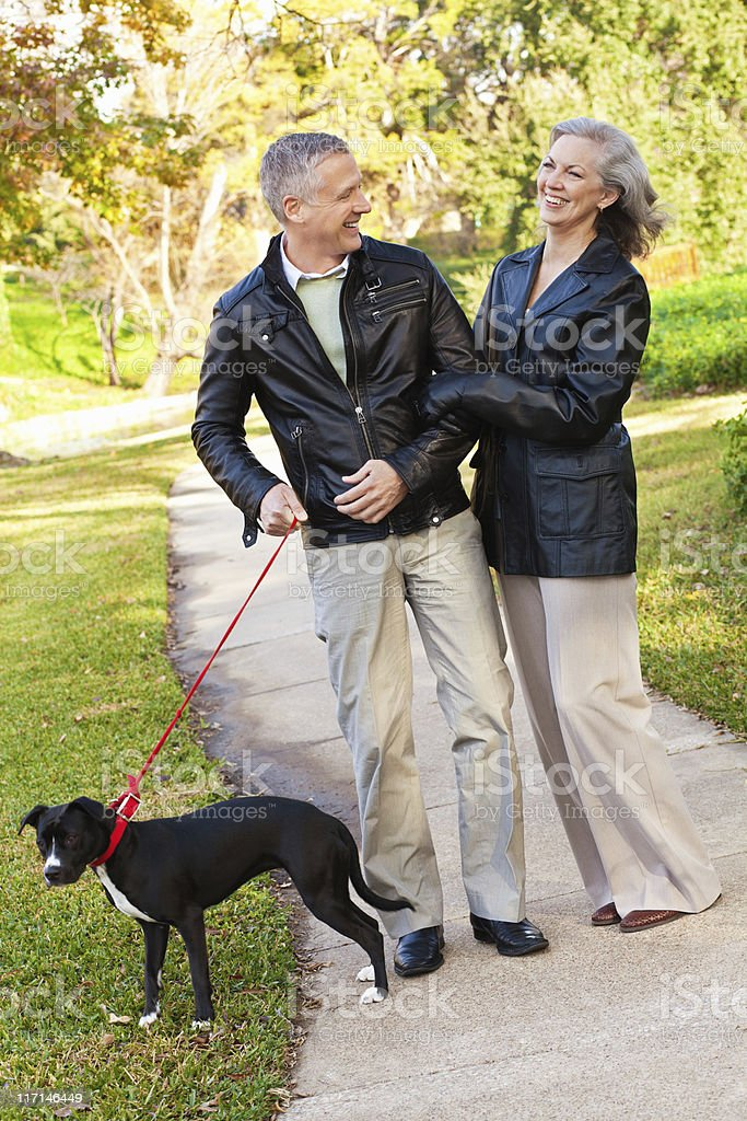 Happy Mature Adult Couple Laughing While Walking Dog at Park.