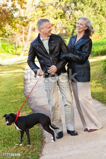 874818944 istock photo Happy Mature Adult Couple Laughing While Walking Dog at Park 117146449