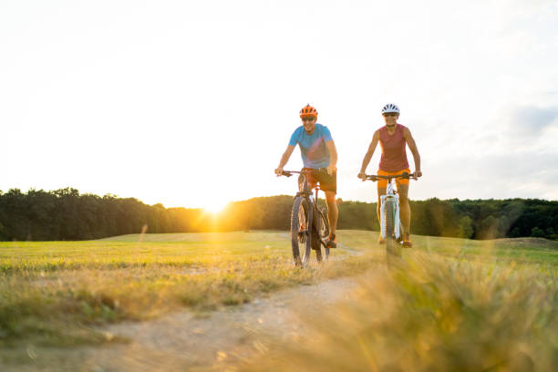 happy mature adult sporty couple on mountainbikes in rural landscape at sunset stock photo