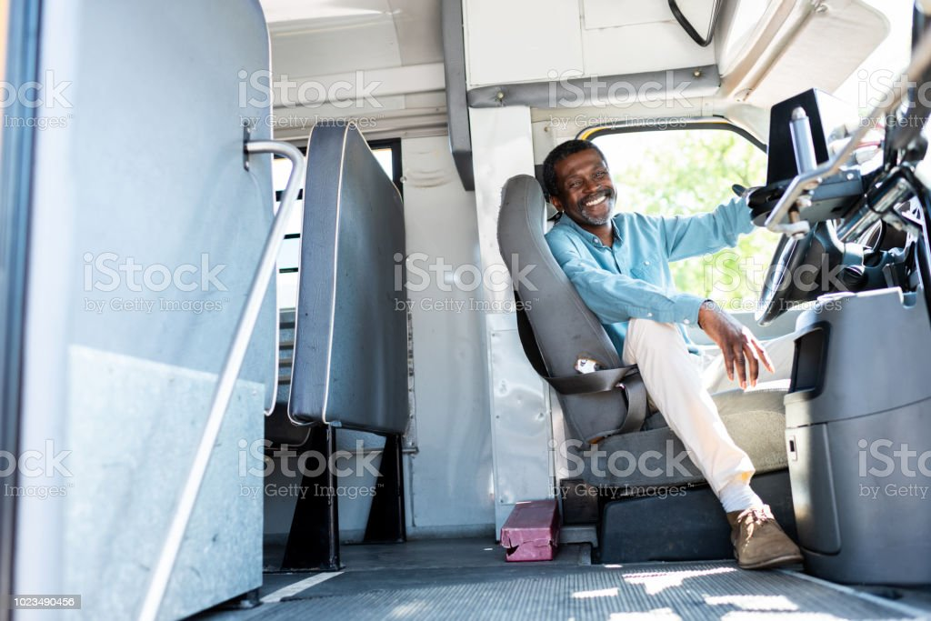 happy mature african american bus driver looking at camera while sitting inside bus stock photo
