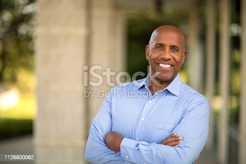 Mature African American man smiling at work.