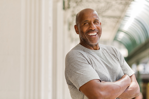 Mature African American man smiling outside.
