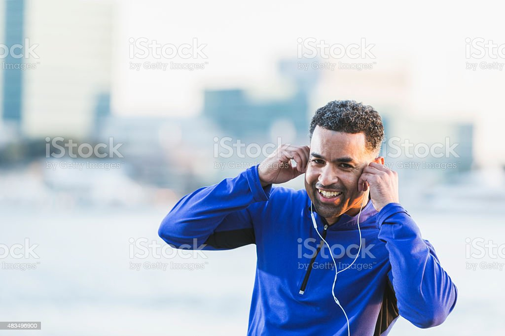 Happy mature African American man with earbuds stock photo