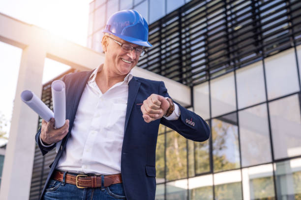 Happy mature architect checking time. stock photo