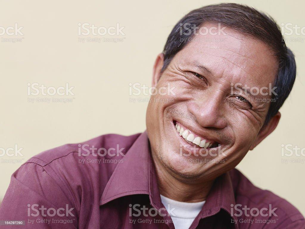 Happy mature Asian man smiling and looking at camera royalty-free stock photo