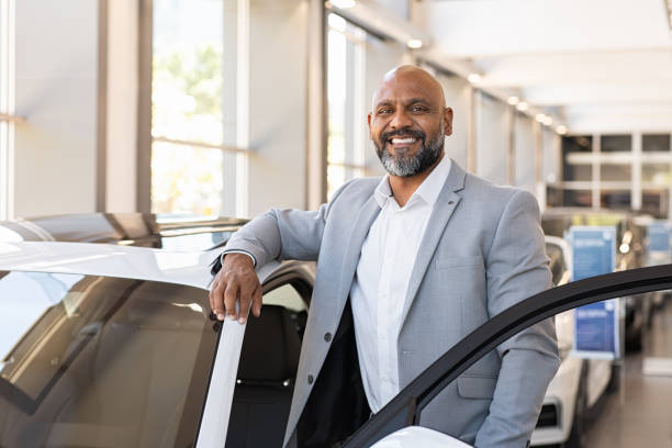 Happy mature black man at car dealership African salesman standing in car showroom near opened door of luxury car. Happy businessman buying his new suv in car salon. Smiling mature man choosing his new car. salesman stock pictures, royalty-free photos & images