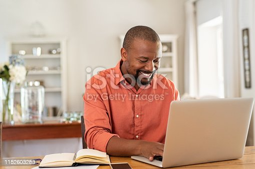 istock Happy mature black man using laptop 1152603283