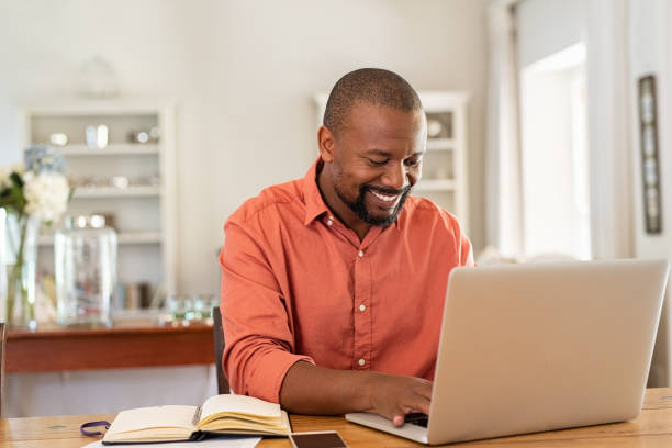 Happy mature black man using laptop Smiling black man using laptop at home in living room. Happy mature businessman send email and working at home. African american freelancer typing on computer with paperworks and documents on table. using computer stock pictures, royalty-free photos & images
