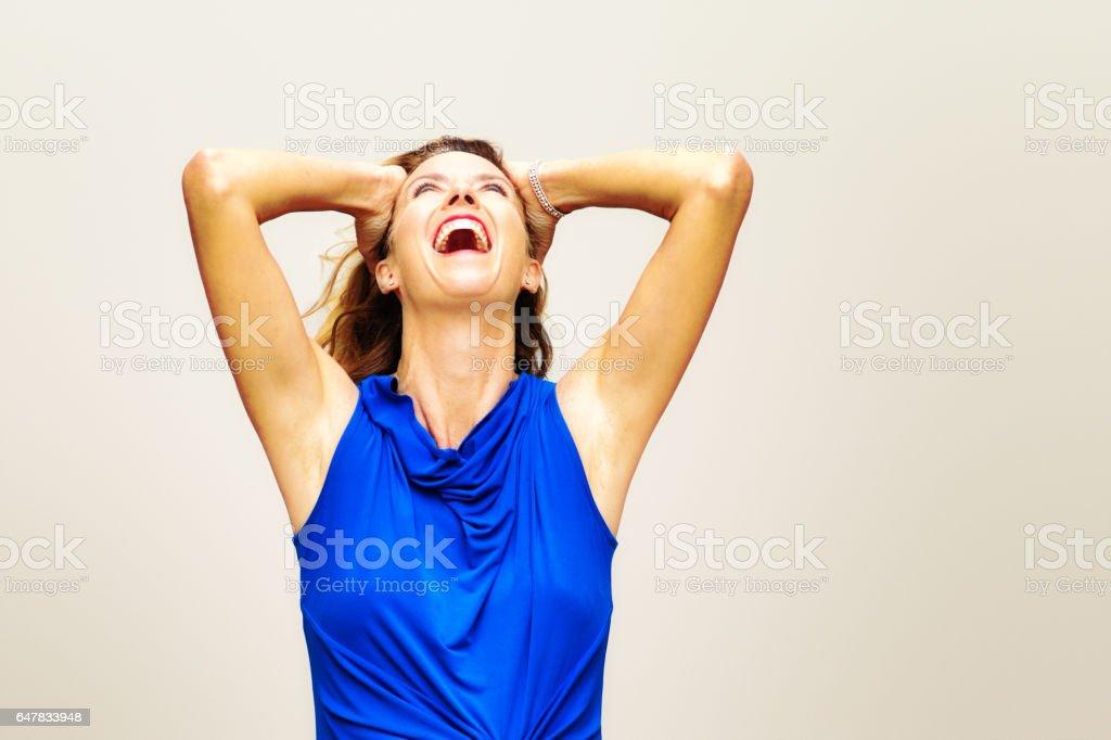 Feliz feminino loiro maduro em azul top rindo olhando as armas - foto de acervo