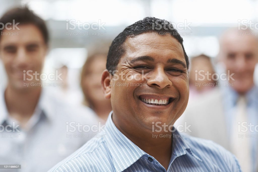 Happy mature business man smiling with colleagues at the back royalty-free stock photo