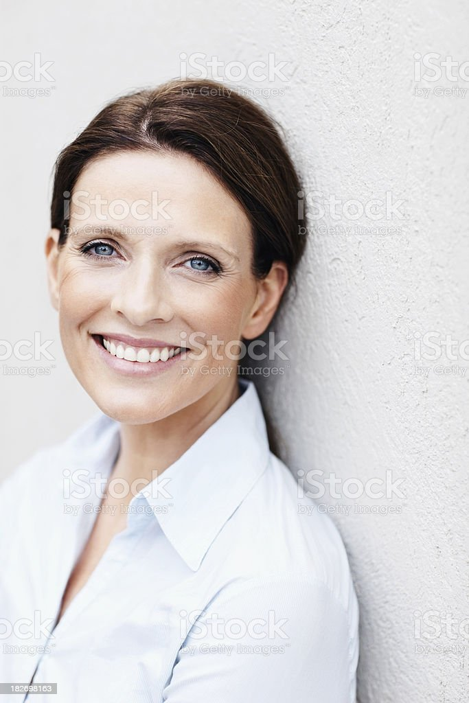Happy mature business woman leaning against a wall stock photo