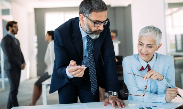 Happy mature businessman and businesswoman planning in office stock photo