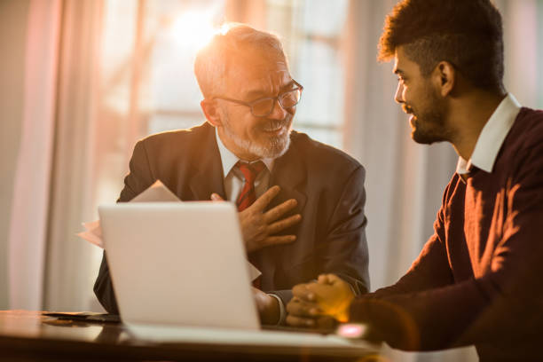 happy mature businessman communicating with his younger coworker in the office. - bankers stock photos and pictures