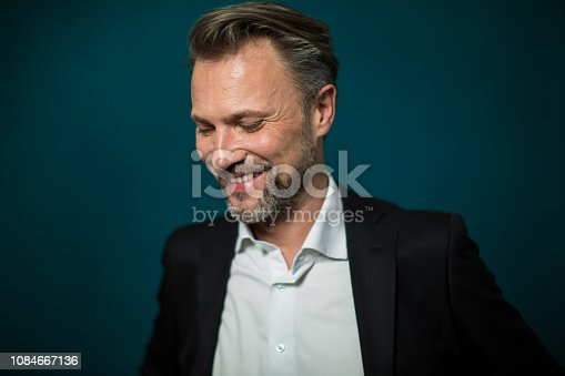 Portrait of happy mature businessman looking down and smiling. Male entrepreneur in suite against green background.