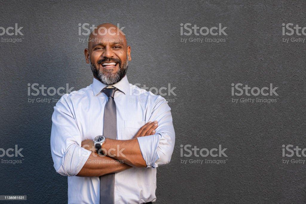 折られる腕と立っている幸せな成熟したビジネスマン - 1人のロイヤリティフリーストックフォト