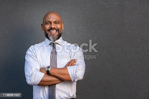 Successful senior man with folded arms standing over grey background. Handsome mature black businessman in shirt and tie looking at camera. Portrait of joyful business man on a grey wall with copy space.